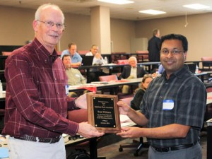 Outgoing Chairman Tom Witham (L) is presented a plaque for his long time service by new Chairman Rajesh Shah